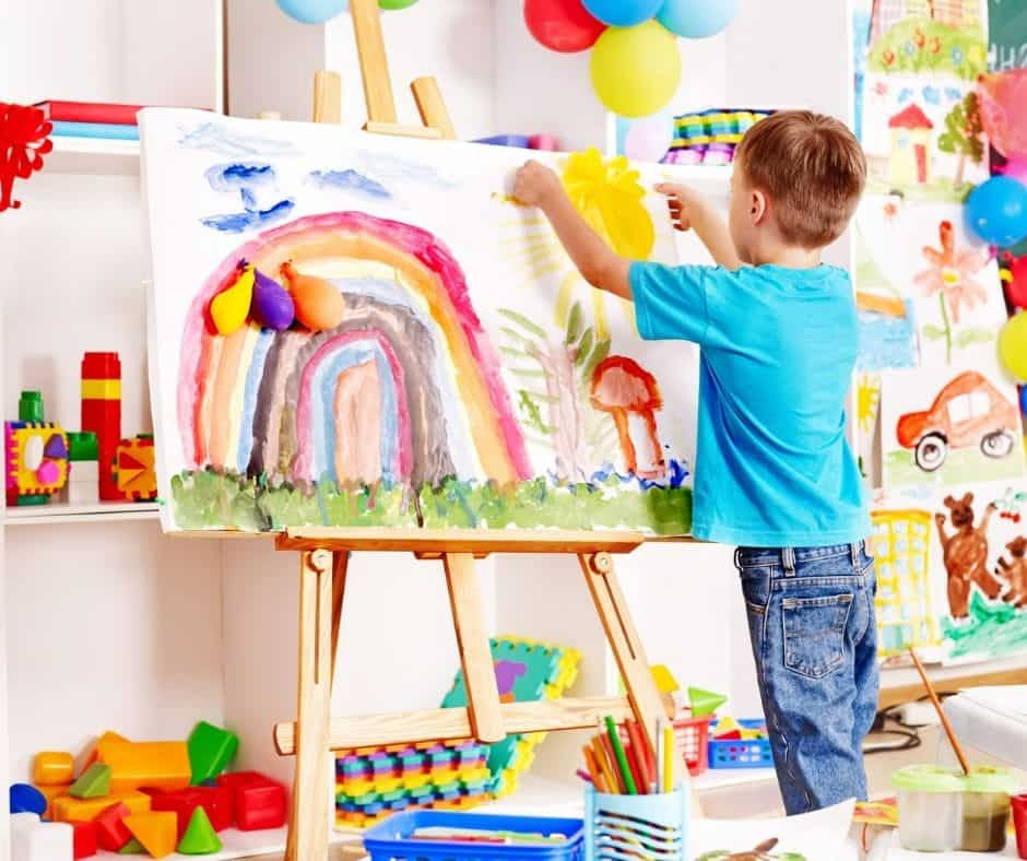 Preschool aged boy painting with art supplies.