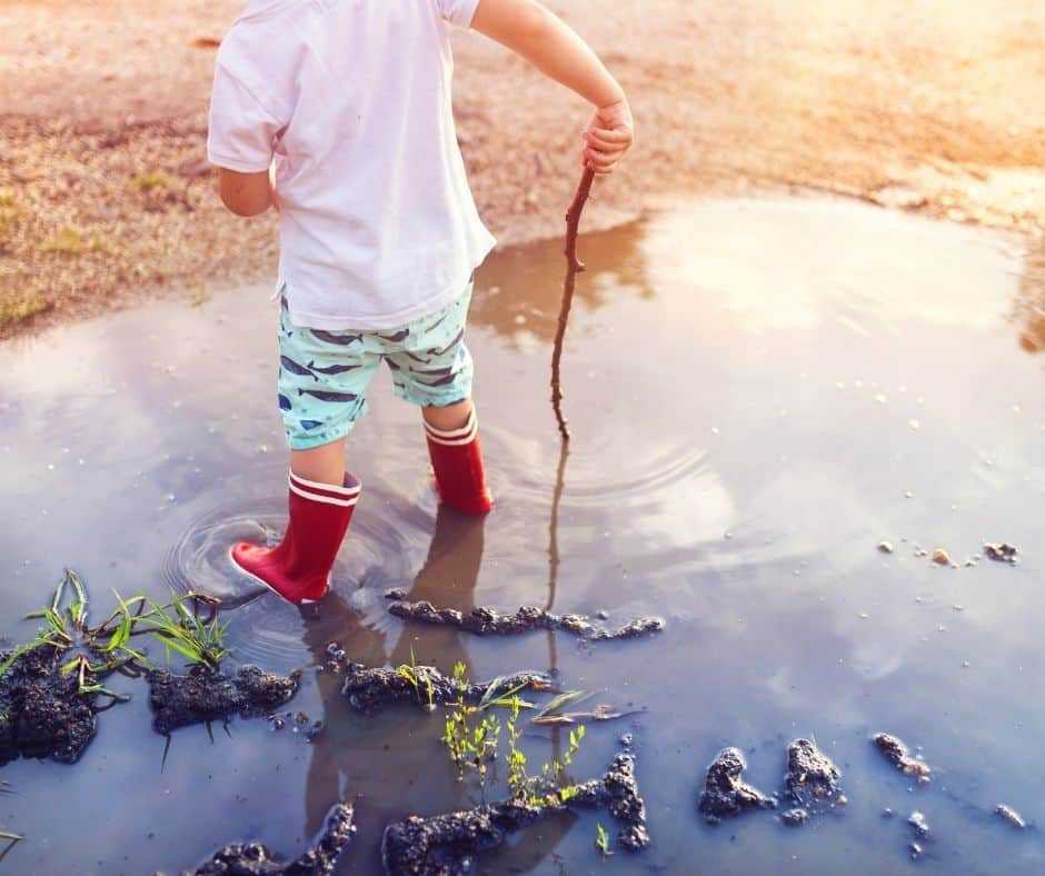 Little boy playing in a puddle of water.