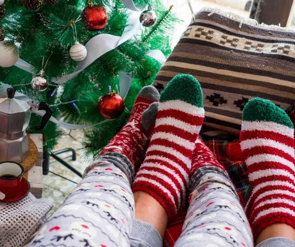 a couple of christmas socks by the christmas tree.