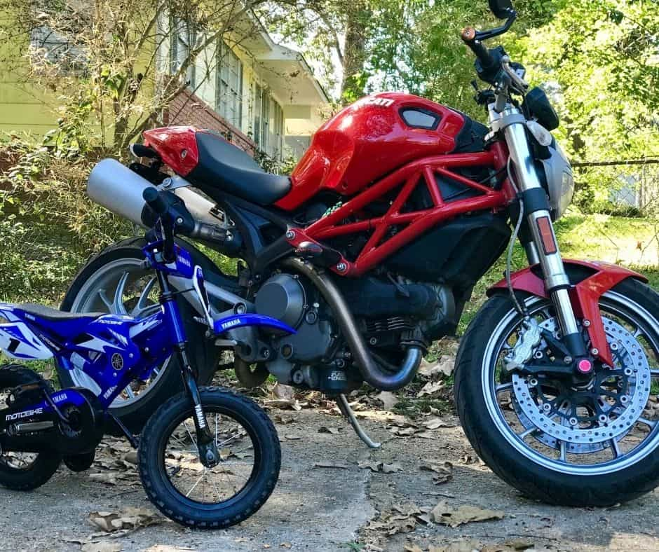 toddler motorcycle next to Ducati Monster red motorcycle.
