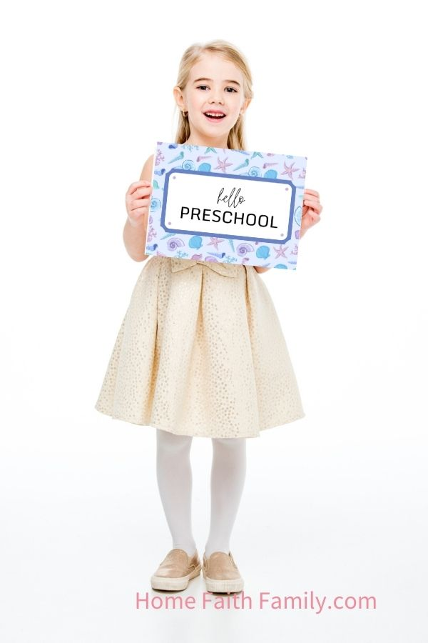 little girl holding a hello preschool sign for her first day of preschool.